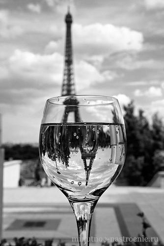 отражение эйфелевой башни в бокале с водой